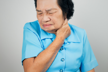 Senior woman suffering from neck pain over white background