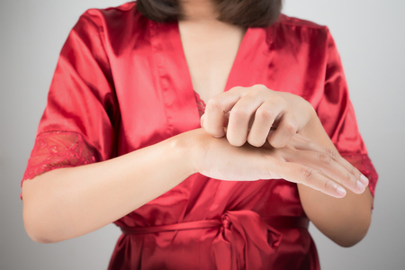 atopic: Woman scratching her arm. Stock Photo