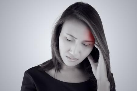 mujer triste: Dolor de cabeza. Mujer asiática que tiene un dolor de cabeza