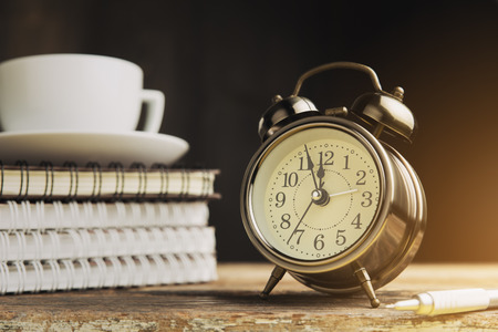 Vintage alarm clock on a table. Photo in vintage color image style