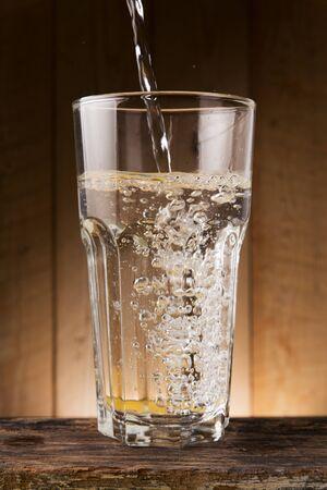 vaso con agua: El agua vierte en el recipiente utilizado en la mesa de madera
