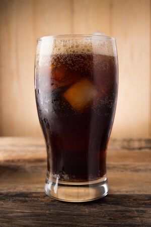 fizzy: Cold fizzy cola soda with ice in glass cup Stock Photo