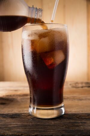 carbonation: Pouring of cola, Cold fizzy cola soda with ice in glass cup
