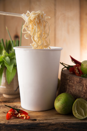 cooked instant noodle: Cup noodle, Cooked instant cup noodle with ingredient on wood background Stock Photo