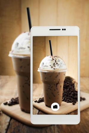 iced mocha with straw in plastic cup on Smartphone Stock Photo