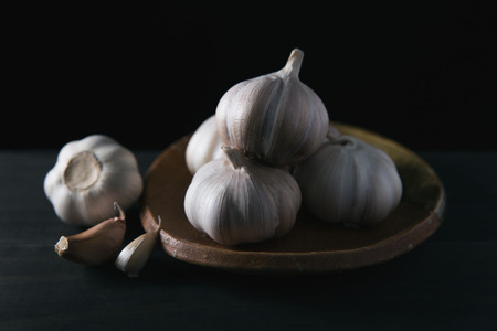 Garlic cloves on wooden vintage background. Stock Photo