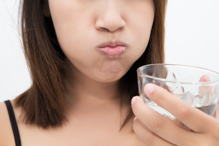 Healthy happy woman rinsing and gargling while using mouthwash from a glass, During daily oral hygiene routine, Portrait with bare shoulders, Dental Health Concepts Imagens