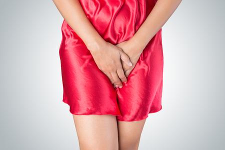 Frau mit Händen halten drückte ihren Schritt Unterbauch. Medizinische oder gynäkologische Probleme, Gesundheitswesen Konzept