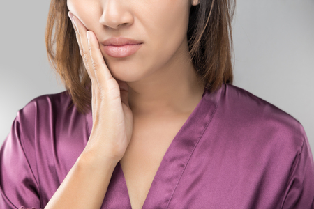 Closeup of beautiful young woman suffering from toothache, Dental health and care, People with teeth problem concept.