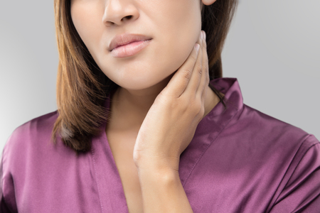 Woman with a sore throat holding her neck, On gray Background, Lymphadenopathy, People with health problem concept. Stockfoto
