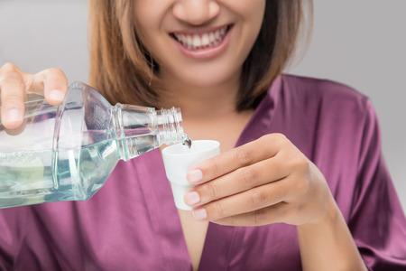 Woman Using Mouthwash After Brushing, Portrait  Hands Pouring Mouthwash Into Bottle Cap, Dental Health Concepts