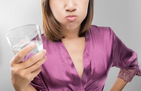 女性は洗浄とうがい毎日の口腔衛生ルーチン、紫のシルクのローブ、歯科医療の概念で女の子の中に、ガラスからうがい薬を使用しながら