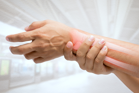 Man massaging painful wrist on a white background. Pain concept Archivio Fotografico