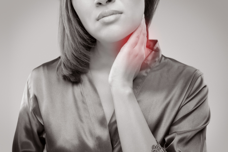Closeup girl with sore throat touching her neck. On gray wall background