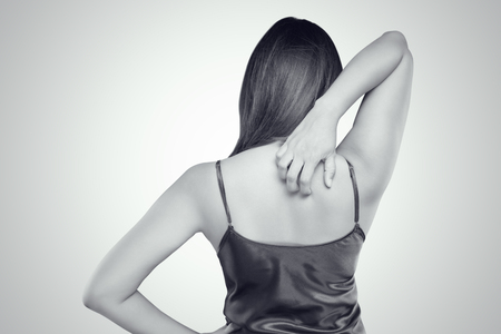 grabbing at the back: Woman scratching her itchy back with allergy rash, Concept with Healthcare And Medicine.