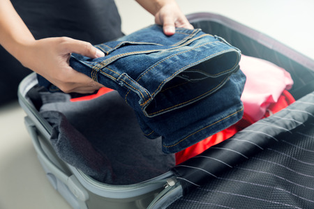 Close up of businesswoman packing clothes into travel bag - Luggage and people concept Stock Photo