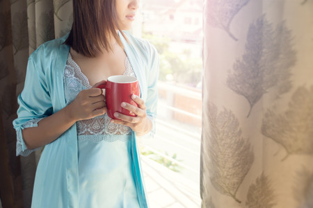1da84f9186 Woman sitting at opened window drinking coffee and looking outside enjoys  of rest Stock Photo