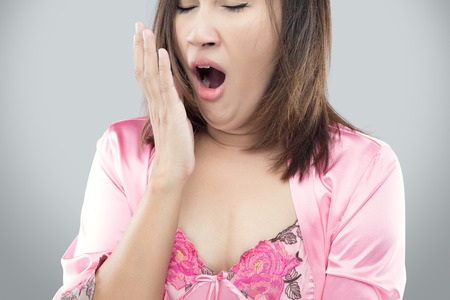 Yawning tired woman. Beautiful asian model isolated on gray background.