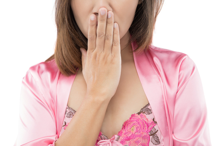 The woman wake up in the morning  and quickly cover your mouth with your hand, isolate on white background. Stock Photo
