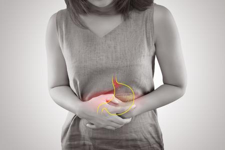 회색 배경, 여성 해부학 개념에 서있는 위식도 역류 질환 또는 산성 역류로 고통받는 여자 스톡 콘텐츠