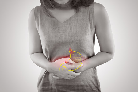 Mujer que sufre de la enfermedad por reflujo gastroesofágico o reflujo ácido de pie contra el fondo gris, concepto de anatomía femenina