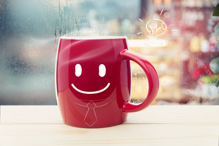 Red mug of coffee with a happy smile, Steaming red coffee cup on a rainy day window background, Good morning and Business concept