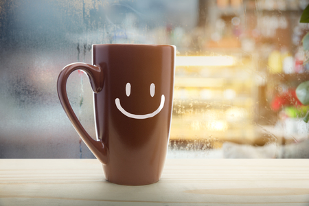 Brown mug of coffee with a happy smile, Steaming red coffee cup on a rainy day window background, Good morning or have a happy day message concept