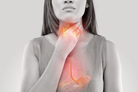 酸逆流や胸焼けに苦しむ女性は、白い背景に孤立