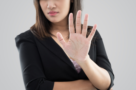 Business woman in black suit showing her denial with no on her hand against gray background