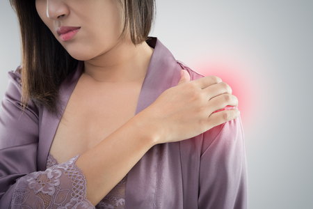 088bc4c679 Asian woman in purple satin nightwear pressing her hand against a painful  shoulder