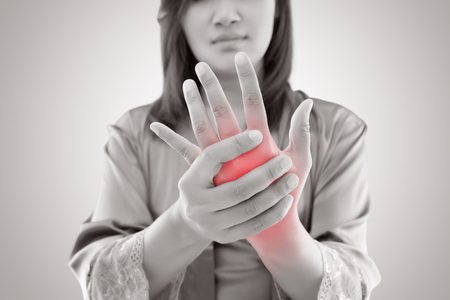 Asian woman holding her hand against gray background , Pain concept Stock Photo