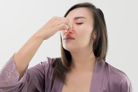 Asian women in satin nightwear with nosebleed against gray background