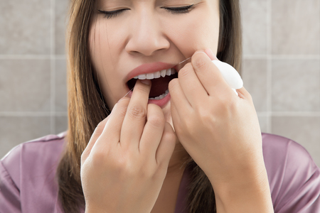 Asian Women In Satin Robes Cleaning Her Teeth Against Gray Background, Woman Flossing Teeth With Dental Floss, Oral Hygiene And Health Care