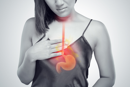 The photo of stomach is on the woman's body against gray Background, Acid reflux or Heartburn, Female anatomy concept Archivio Fotografico
