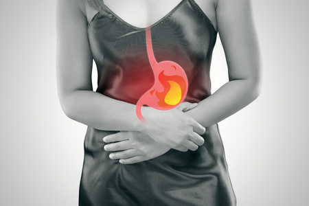 Acid reflux or Heartburn, The photo of stomach is on the womans body against gray Background, Bad health, Female anatomy concept Stock Photo