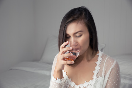 Asian woman in white nightgown drinking water on the bed at bedroom