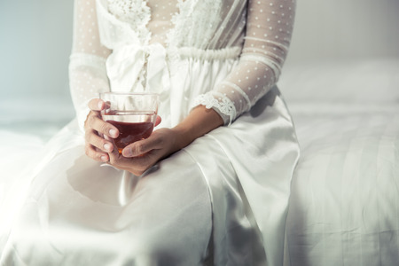 Female in white nightwear hand holding a glass of clean water in the bedroom