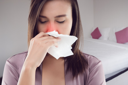 Asian women in satin nightwear feeling unwell and sneeze at bedroom, Dust allergies symptoms, People caught cold and allergy