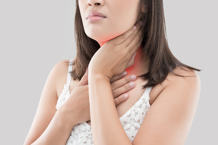 Asian woman with sore throat or neck pain or thyroid gland against gray background. People body problem concept