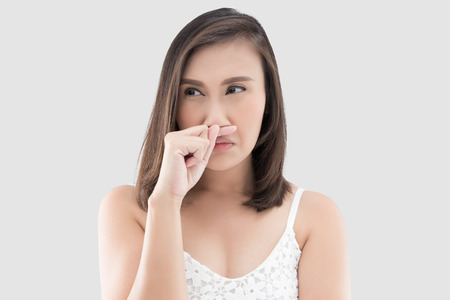 Asian woman in white dress catch her nose because of a bad smell against gray background