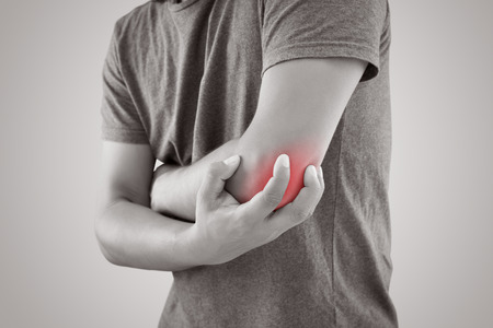 Asian man with pain in elbow against gray background. People suffering from chronic joint rheumatism. Body & Health concept