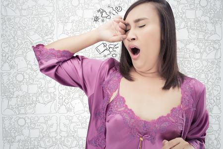 Asian women in purple sleepwear yawning against cartoon background, Health balance sleep deprivation concept