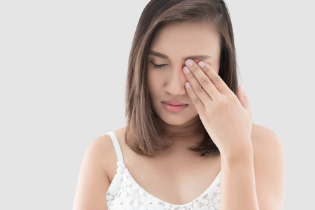 Asian woman suffering from strong eye pain against gray background. Female has a pain in the eye. Healthcare concept. Having migraine Stock Photo