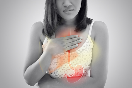 Woman suffering from Acid reflux or Heartburn against gray background / Asian people with symptomatic Indigestion or Gastritis