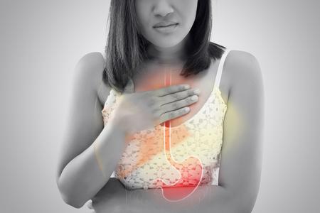 Femme souffrant de reflux acide ou de brûlures d'estomac sur fond gris / personnes asiatiques avec une indigestion symptomatique ou une gastrite