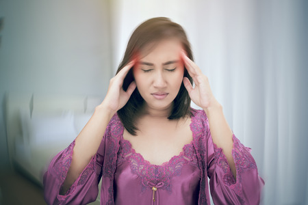 Asian woman has headache at bedroom, Benign Paroxysmal Positional Vertigo: BPPV, Concept with Sickness and Healthcare. Stock Photo
