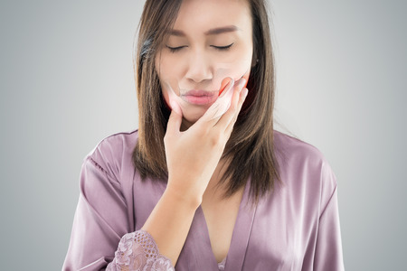 Temporomandibular Joint and Muscle Disorder: TMD, Suffering from toothache. Beautiful young woman suffering from toothache while standing against grey background Standard-Bild