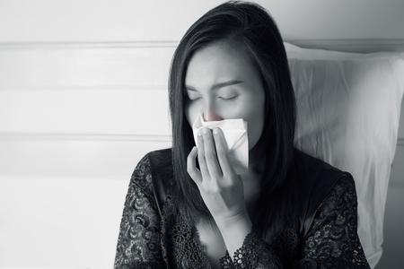 Asia women feeling unwell and sinus. Thai people get nose allergy. Flu sneezing nose sitting at the bedroom