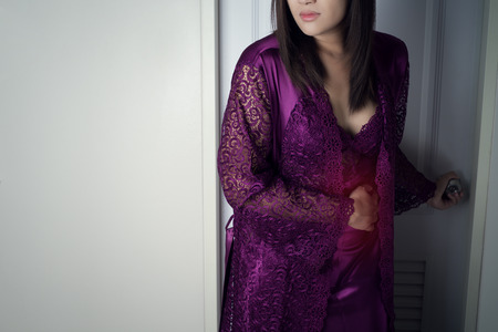 Asian woman in purple long nightwear and lace robe touching belly painful suffering from stomachache causes of menstruation period. Thai lady left the toilet at midnight. Diarrhea or gastrointestinal system desease. Concept with healthcare and lifestyle.