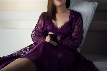 Asian woman in purple nightgown satin holding remote controller watching television in her bed at night. Bored people watching television in bedroom Stok Fotoğraf